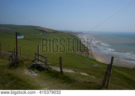 Scenic Coastal View Of Isle Of Wight Featuring The Ocean, A Narrow Beach On The Foothills Of Cliffs.