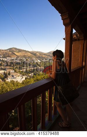 Andalucia, Spain 07/13/2010: A Young  Woman In Summer Clothes Is Leaning On The Railings Of A Balcon