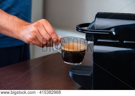Close Up Of Hand Picking Up A Cup Of Espresso Of Capsule Coffee Machine At Home. Concept Of Coffee B