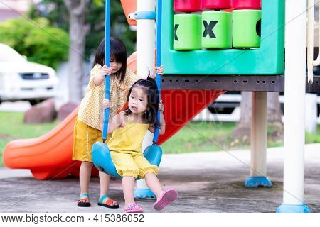 Sister Is Teaching Sister To Play Swing. Kid Helped Hold String Of Blue Swings So That Baby Could Si