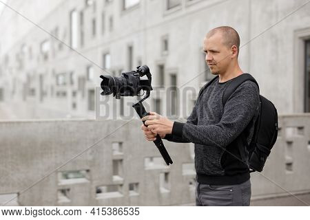 Filmmaking, Hobby And Creativity Concept - Side View Of Professional Videographer Shooting Video Usi