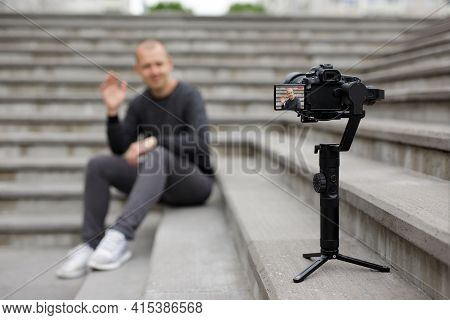 Videography And Blogging Concept - Male Blogger Sitting On Concrete Stairs And Recording Video With