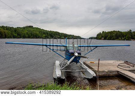 Small Seaplane Moored To A Floating Pontoon Near The Shore Of A Mountain Lake. Adirondacks, Ny