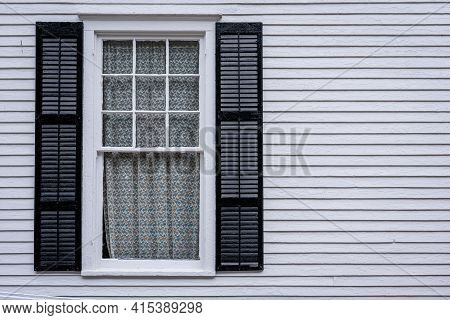 Window With Open Shutters Of An White Colored Wooden House