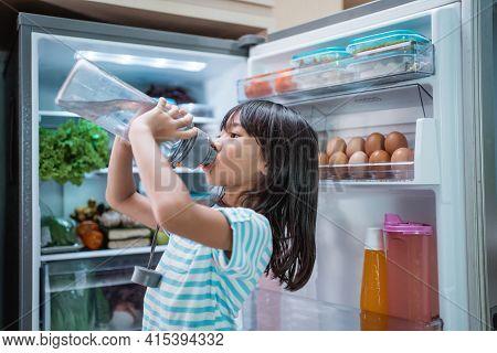Asian Girl Open Fridge Door Drinking A Bottle Of Water