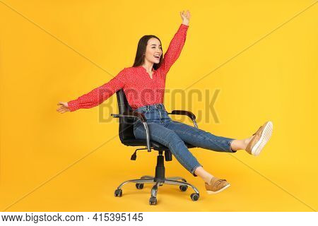 Young Woman Riding Office Chair On Yellow Background