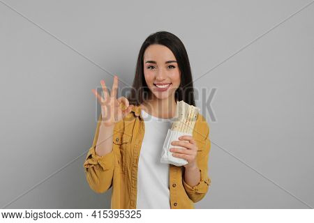 Happy Young Woman With Tasty Shawarma Showing Okay Gesture On Grey Background