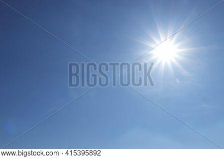 Bright Sun In Blue Sky. Halo Effect