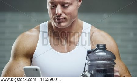 Fit Man At Workout In Gym With Cell Phone And Shaker. Bodybuilding And Healthy Lifestyle Concept Bac