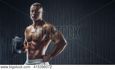 Fit Man At Workout In Gym With Shaker. Bodybuilding And Healthy Lifestyle Concept Background. Muscul
