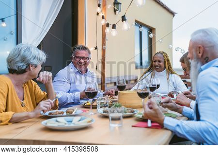 Happy Multiracial Senior Friends Having Fun Dining Together On House Patio - Elderly Lifestyle Peopl