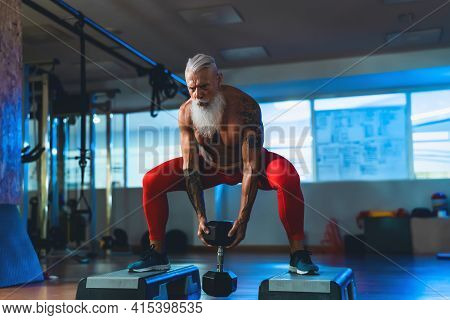 Senior Man Doing Workout Exercises Inside Gym - Fit Mature Male Training In Wellness Club Center - B
