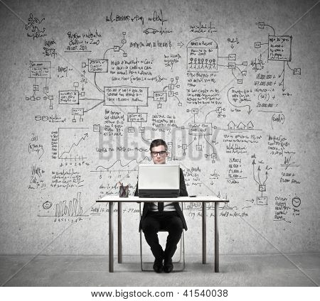 Businessman working at a laptop with in the background a wall full of economy drawings
