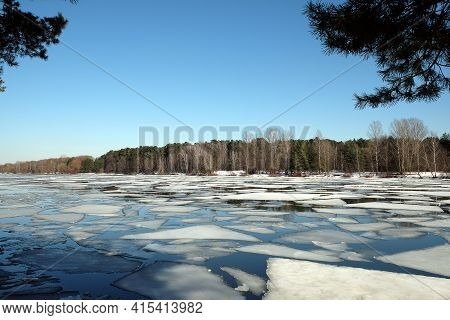Beautiful Natural Landscape With Ice Drift On The Spring River And Forest Trees On Opposite Bank Und