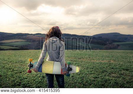 Girl In Sweatshirt Walking Across Green Field Towards Hills (out Of Focus). Girl\'s Hair Flutters In