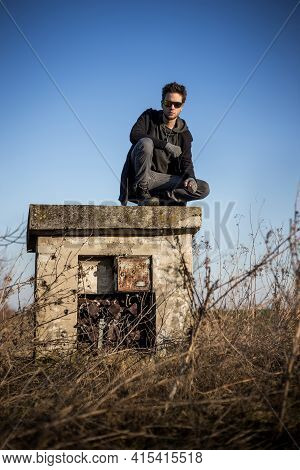 Young Man Posing In Setting Sun Light. Man Is Wearing Militant Style Clothing, Squatting On Old Aban