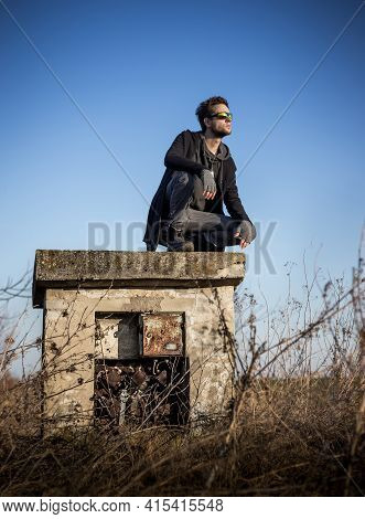 Young Man Looking Towards The Setting Sun. Man Is Wearing Militant Style Clothing, Squatting On An O