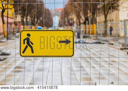 Building Fence Directing Pedestrians. Yellow Sign With The Direction Of Pedestrian Traffic