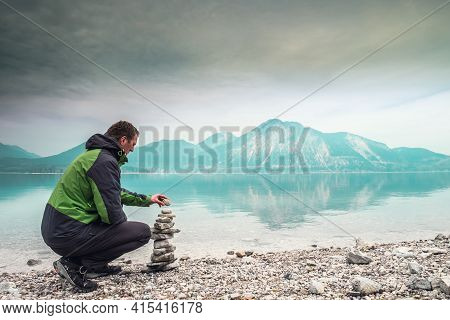 Cairn Building. Hiker Builds Rock Cairn From Sharp Dolomit Stones At Alpine Lake. Spring In European