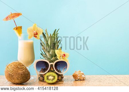 Pina Colada Cocktail Drink, Pineapple With Sunglasses And Coconut, Blue Background, Copy Space. Summ