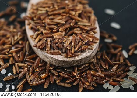 Spoon With Brown Rice Spilled Grains. High Quality And Resolution Beautiful Photo Concept