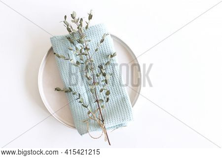 Closeup Of Green Eucalyptus Leaves Branches, Earthenware Plate And Blue Cotton Towel On White Table
