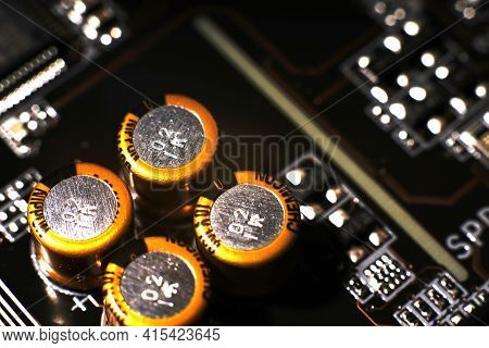 Moscow, Russia - March 3 2021: Four Gold-colored Closeup Capacitors. Dimmed Lights