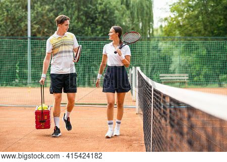 Young Couple On Tennis Court. Man And Woman Leaving The Court After The Game