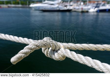 Yachting And Marine Concept. Close-up Of A Sea Knot On A Blurred Background Of Boats Moored In The H