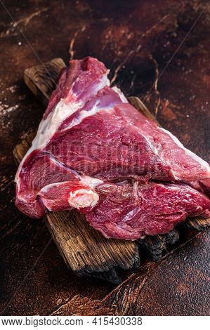 Raw Lamb Mutton Thigh On Butcher Table. Dark Background. Top View
