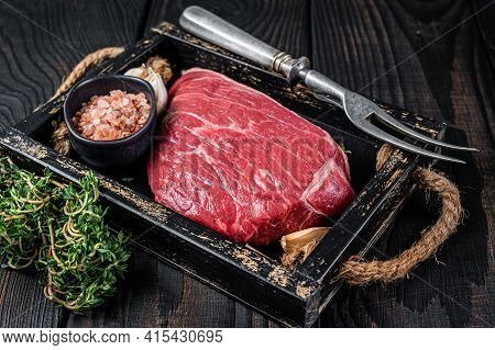 Raw Top Sirloin Cap Beef Cut Meat Steak Or Picanha In Wooden Tray With Herbs. Black Wooden Backgroun
