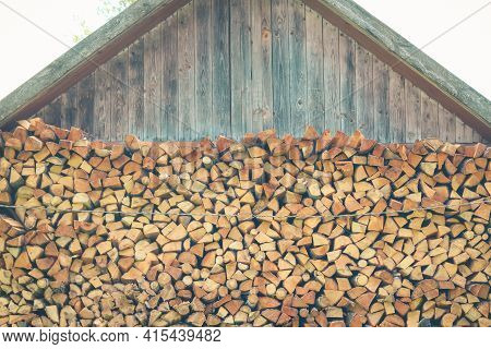 Firewood Or Fuelwood Stacked By A Wall. Wooden Pile Prepared For Winter. Fuel For Countryside Firepl