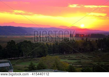 The Sun Sets Behind The Mountains In The Tropics. Sunset In Pitsunda. Mountains And Plains With Euca