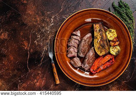 Grilled Mutton Tenderloin Fillet Meat, Lamb Sirloin On Rustic Plate With Vegetables. Dark Background