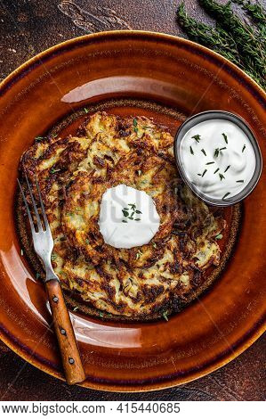 Potato Pancakes Or Fritters With Cream Sauce In A Rustic Plate. Dark Background. Top View