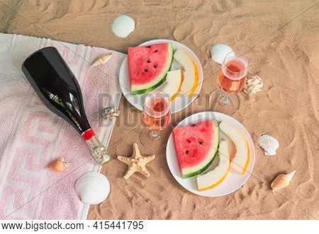 Glasses Of Rose Champagne, Plates With Slices Of Watermelon And Melon, Bottle Of Champagne, Starfish