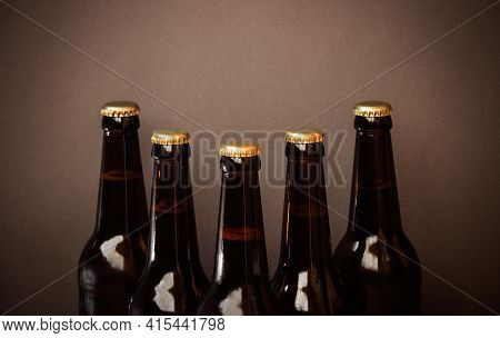 Glass Bottles Of Beer On Brown Background. Selective Focus. View With Copy Space.