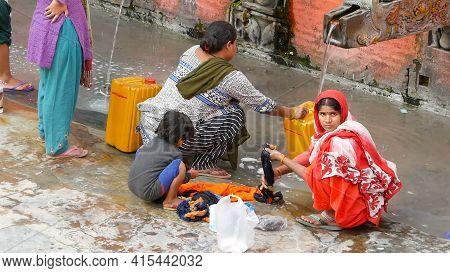Lalitpur Patan , Nepal - 12 October 2018 People Washing Near Temple Wall. View Of Women Washing Hair