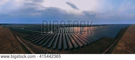 Aerial Panorama View Into Large Solar Panels At A Solar Farm At Bright Sunset. Solar Cell Power Plan