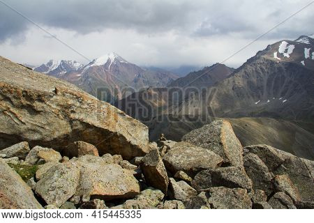 A Large Pile Of Huge Stones In The Foreground, In The Distance The Snow-capped Peaks Of The Ridges A