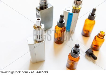 Vaping Device E-cigarette Electronic Cigarette And Liquid Bottles Isolated On White Background. Vape