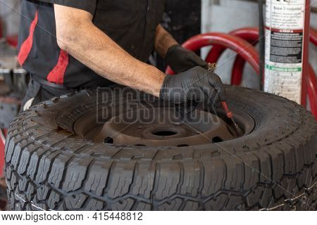 Mechanics Gloved Hand Adjusts The Inflated Tire Pressure Of Vehicle Front Tire During Routine Brake