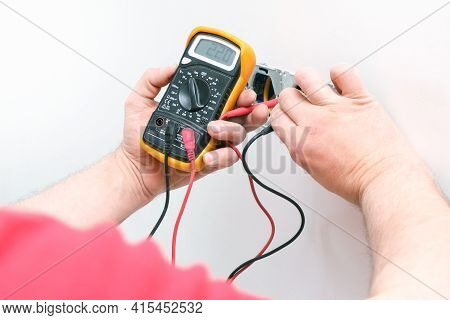 Electrician A Wall Socket With Electronic Multimeter. Wire And Multimeter In Hands Close Up