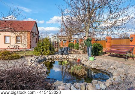 Middle-aged Caucasian Man Cleans A Garden Pond With Leaf Rake From Water Plants And Falling Leaves N