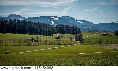 Landscape Scene With Agriculture Field, Trees, Road, Snow Covered Mountains And Sky. Switzerland. Tr