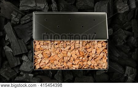Close Up One Stainless Steel Metal Smoker Box With Hardwood Alder Chips On Black Lump Charcoal Piece