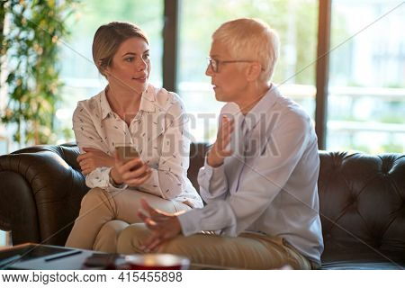 Senior female partner mentoring young businesswoman in the office