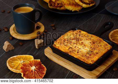 Curd Casserole And A Cup Of Coffee On A Black Table. Breakfast Serving.