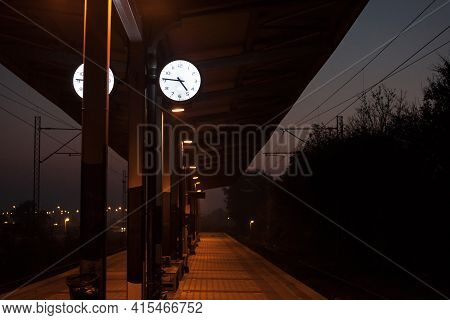 Analog Clock On The Platform Of A Commuter Train Station At Night, During A Dark Sunset Evening, Ind