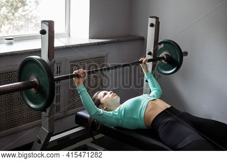 A Young Athletic Woman Does A Bench Press. Athletic Strong Woman